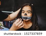 Small photo of Young Asian Chinese girl with skeleton face make up. Make-up artist holding brush to paint mouth area. Skeleton design for chinese girl in Asia. Outdoor studio in the street. Drama competition.