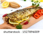 Stock photo baked herring with lemon and spices on a white wooden background tasty fish dish 1527896009