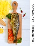 Stock photo baked herring with lemon and spices on a white wooden background tasty fish dish top view 1527896030