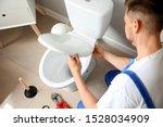 Plumber Installing Toilet In...