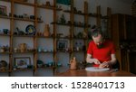 Small photo of Professional male potter shaping and scraping dry clay cup with special tool in pottery workshop, studio. Crafting, artwork and handmade concept
