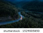 Aerial view of a sharp turn on a mountain road among green forest trees. Semi truck with cargo trailer and bright headlights on a dark highway. P-258 road near Baikal shore in Siberia, Russia