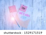 Small photo of Conceptual hand writing showing Want To Know A Secret Question. Business photo text to divulge a confidential vital information Envelope blank sheet sticky note ballpoint wooden background.