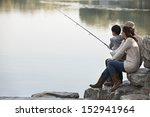 Family Fishing Off Of Rocks At...