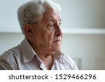 Small photo of Elderly man feels sad and lonely looks away close up face, grey haired 70s grandfather thinking about disease or recollect life in nursing home care, concept of medicine for seniors, medical insurance