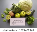 Small photo of Green vegetables and fresh fruits containing vitamin K with structural chemical formula of vitamin K molecule. Natural products rich in vitamin K, healthy nutrition concept.