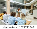 Small photo of Pensive pretty girl wears white blouse, pointing at flip chart, stretches palm towards people waiting for answer, looks down thoughtfully, stands in the middle of roomy class