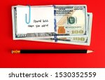 Small photo of An amount of cash dollars money clipped with a white note pad written SPEND LESS THAN YOU EARN with a pencil under and red background , concept of remind oneself a motto to spend less and save more