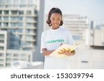 Small photo of Happy altruist woman holding notebook outdoors on urban background