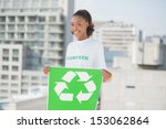 Small photo of Happy altruist woman holding recycling sign outdoors on urban background
