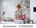 Small photo of Finding nasal spray. Red-haired woman taking nasal spray out of first aid kit while having stuffy nose