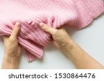 Woman hands holding the knitted thing with hole made by moth