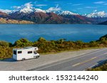 A white camper-van / RV parked in a lay-by viewpoint on the banks of Lake Wanaka with the lake and the dramatic snow capped peaks in the distance. - stock photo