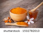 Small photo of Turmeric ( curcumin, Curcuma longa Linn) powder in wooden bowl and scoop with rhizome and glass of honey isolated on old wood table background. Beauty and spa concept.