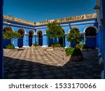 Inner courtyard of rooms with blue walls and a central tree.  Saint Catherine Monastery (Convento de Santa Catalina), Arequipa City, Peru