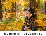 Little Cowboy Boy Sitting In...