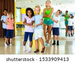 Small photo of Group of happy cheerful children practicing vigorous jive movements in dance class with female coach