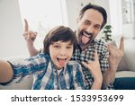 Small photo of Hey there followers! Close up photo of positive cheerful handsome guy dad making hard punk symbol and his little son taking selfie on smartphone showing tongue in room indoors