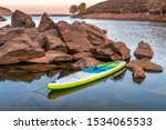 inflatable stand up paddleboard on a rocky shore of mountain lake - Horsetooth Reservoir in northern Colorado in fall scenery