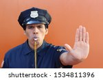Small photo of Policeman blowing whistle and showing stop hand gesture