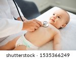 medicine, healthcare and pediatrics concept - close up of female doctor with stethoscope listening to baby girl's patient heartbeat or breath at clinic or hospital