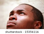 a young man looks up to the sky while deep in thought - stock photo
