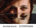 Small photo of Woman eyes close up reflected in mirror. Hypnotize strong look. Hypnotic deeply penetrating glance. Revengeful insidious expectant gaze. Young caucasian girl face. Horizontal portrait. Good vision