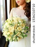 Small photo of Bride with her whir rose bouquet on wedding day