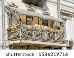 Small photo of Antique vintage balcony disfigured by inept renovation
