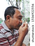 Small photo of surabaya-indonesia. 29 April 2012. A man is smelling a cigarette before he gets removed from smoking. rokon is detrimental to health.