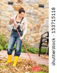Smiling Woman Raking Leaves...