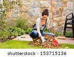 Young Woman Raking Leaves...