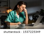 Small photo of attractive and tired nurse in uniform sitting at table during night shift