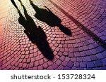 People walking, casting shadows on cobblestones - stock photo
