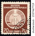Small photo of SINGAPORE - OCTOBER 21, 2019: A stamp printed in Germany shows DDR national coat of arms with inscription Service Stamp, series GDRs national coat of arms, circa 1952