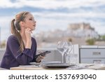 Small photo of Blonde looking straight ahead while sitting holding a phone in one of her hands while the other hand places her chin debase.