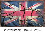 Small photo of barbed wire in front of an old stained dirty union jack british flag with dark crumpled edges on a brick wall background brexit freedom of movement isolationist concept