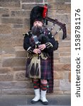 Small photo of EDINBURGH,UK - AUGUST 14,2019 : Bagpipe player in traditional scottish kilts in Edinburgh