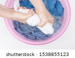Small photo of Female hands wring out white clothes on a background of a basin with blue linen close up, top view