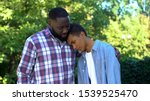 Small photo of Kind father hugging teenage son admitting guilt, child upbringing, parenting