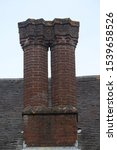 Small photo of A pair of brick Tudor chimneys from an English manor house. A pair of Tudor chimneys from the top of a manor house.