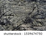 Rugged rock background - dark bedrock with many cracks and crevices - greys and blacks color - Tofino, Vancouver Island, BC, Canada