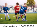 Small photo of Kids Kicking Football Ball. Boys Play Soccer on Grass Field. Spectators Parents in the Background. Youth Players kicking Soccer Match on grass Stadium. Youth Football Tournament