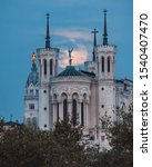 Small photo of Fourviere basilica at sunrise with the full moon setting behind the chucrch, creating a holy feeling, glorification of St. Michael and the statue of Virgin Mary. Peace, quietness, greatness, spiritual