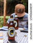 Small photo of Nairobi, Kenya, July 11 2017 - Tourist enjoys the local beer Tusker