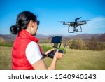 A woman is piloting a drone driving it from a remote control. - stock photo