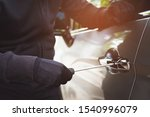 Small photo of Close up car thief wearing black clothes hand holding screwdriver tamper yank and glove stealing automobile trying door handle to see if vehicle is unlocked trying to break into. car theft concept.