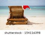 Santa hat on chaise longue on white sand beach - stock photo