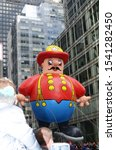 Small photo of New York, NY / USA - November 26, 2015: The popular Harold the Fireman balloon floats majestically past New York City's skyscrapers during the annual Macy's Thanksgiving Day parade.