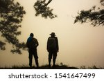 Silhouette Two Man Trekking On...